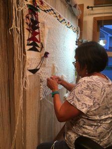 Weaving Apprentice Kim Seward at the halfway point of her beautiful weaving.