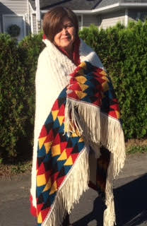 Chief Janice George modelling the master weaving created for CCNA: Restoring the Breath-Sacred Relationship at The Portland Art Museum